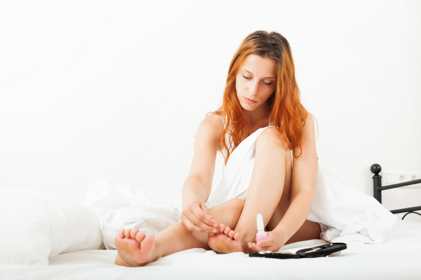red-haired  woman looks at her toenails